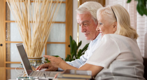 Older couple using their laptop to access GP Services